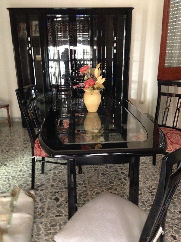 Tavolo, sedie e vetrina laccate nero lucido