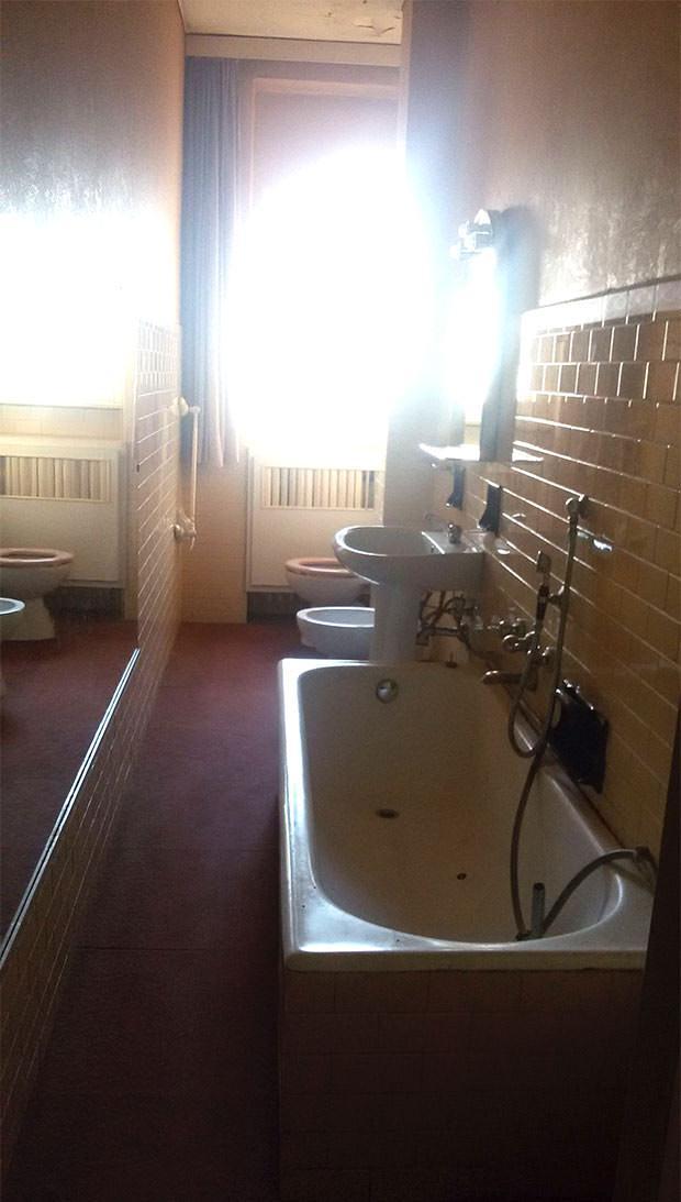 Doccia in bagno stretto e lungo con finestra in legno e termosifone