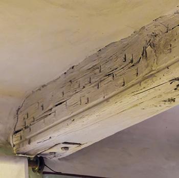 Una trave in legno con evidenti lesioni.