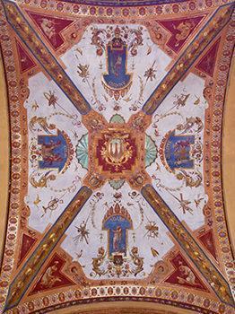 Decorazioni a grottesche con stemmi araldici, figure di santi ed eroi mitologici nel portico di un edificio di stile eclettico.