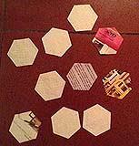 Esagoni di carta con lato di 3 cm, su cui andrà imbastita la stoffa.