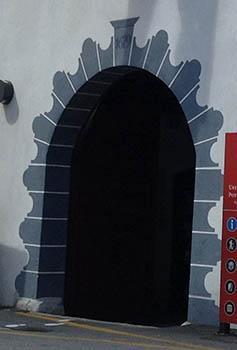 Edificio di Caporetto (Slovenia) con portale ornato da un bugnato dipinto molto stilizzato.