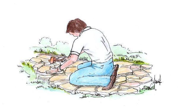 Prima fase di posa delle pietre irregolari per vialetto in giardino