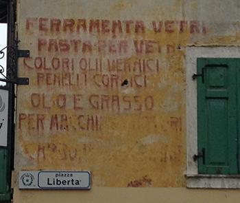 Elenco di merci vendute in un particolare negozio, visibile su una casa del centro storico di Pinzolo.