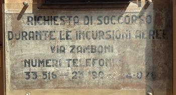Avviso con l'indicazione dei numeri del soccorso antiaereo, visibile in un edificio del centro storico di Bologna.