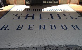 Insegna di un albergo diurno visibile nel pavimento di un portico di Bologna.