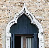 Finestra di stile gotico veneziano con arco trilobato.