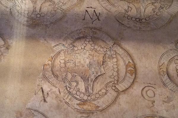 Particolare di una finta tappezzeria quattrocentesca con monogrammi e stemmi araldici (Castello di Bazzano).
