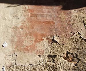 Facciata decorata a calce con un motivo (molto degradato) a finto mattone.