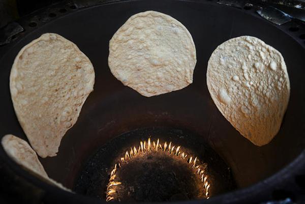 La cottura del tipico pane indiano in forno tandoori di tipo tradizionale.