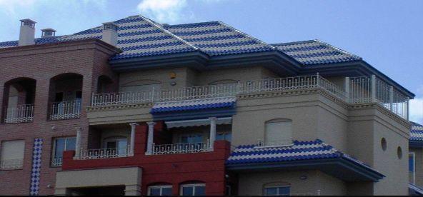 Tetto di edificio moderno con motivi decorativi formati da tegole di due colori. Una realizzazione dell'Azienda Tejas Borja.