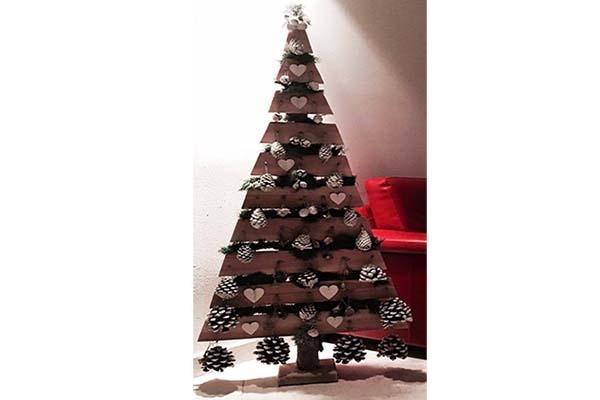 Albero di Natale realizzato in legno con decorazioni con pigne. Di ...