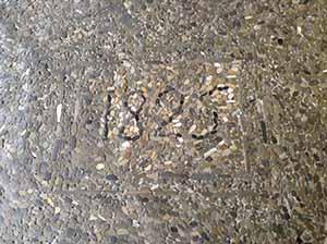 Pavimento in ciottoli con data di realizzazione. Bologna, portico in Piazza Malpighi.