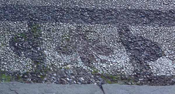 Pavimentazione in ciottoli bicroma con il giglio di Firenze. Firenze, vicino a San Miniato al Monte.