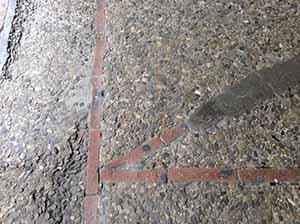Pavimentazione in ciottoli con porzioni smosse e integrazione in materiali incongrui, e perciò bisognosa di restauro.