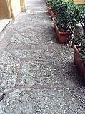 Pavimentazione in ciottoli e mattoni con motivi geometrici.