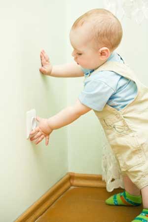 Immagine di bimbo che sta per inserire le dita nella presa