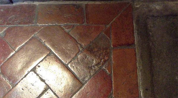 Pavimento in tavelle di cotto con disposizione a spina pesce e cornice di bordatura. Firenze, Palazzo Davanzati.