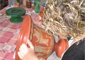 Una vasaia dell'azienda Kentos decora un vaso in stile attico.