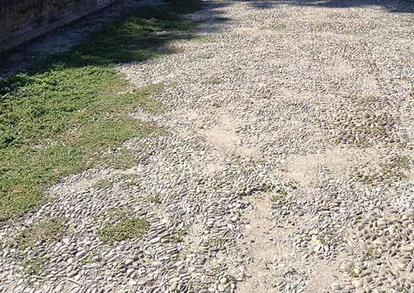 Pavimentazione esterna in ciottoli con lacune.