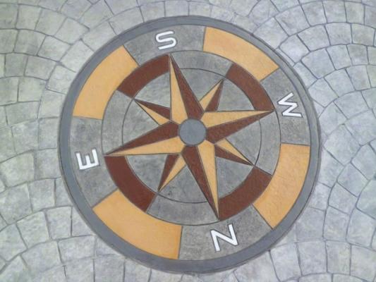 Dettaglio di pavimento in calcestruzzo stampato con rosa dei venti, di Isoplam.