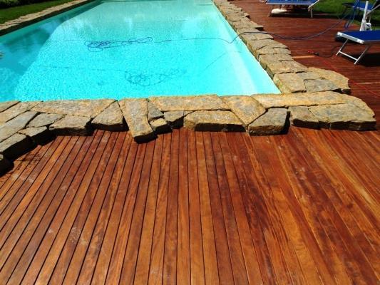 Particolare bordo piscina realizzato da Artwood in iroko e pietre