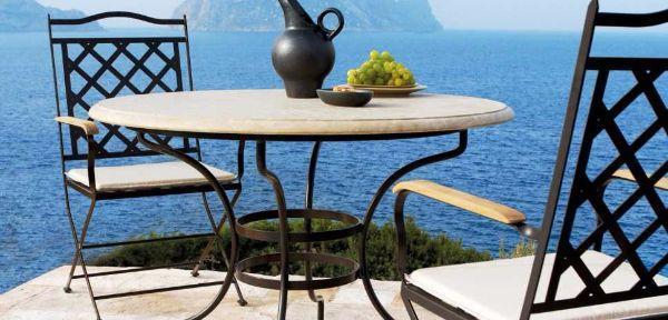 Tavolo in ferro battuto con piano in pietra e sedie, modello Capri Manutti