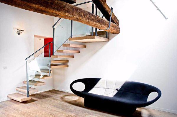 Ambientazione living con scala in legno e vetro di Officine Sandrini