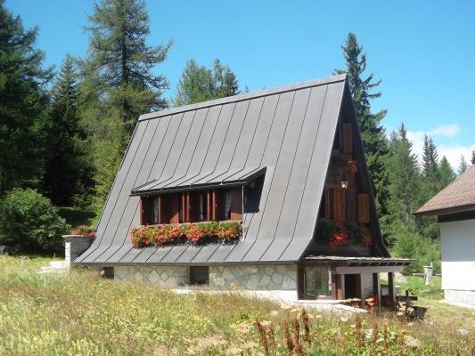 Una casa a motta di Sotto (SO) con un tetto molto inclinato in rame, adatto per zone fredde e nevose