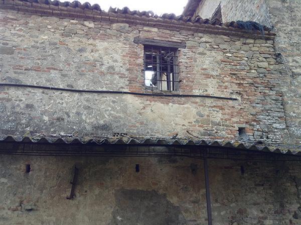 Edificio rurale abbandonato con tetto completamente crollato
