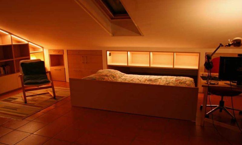 Zona notte in mansarda con i mobili su misura a scomparsa di Zaccaria Monguzzi