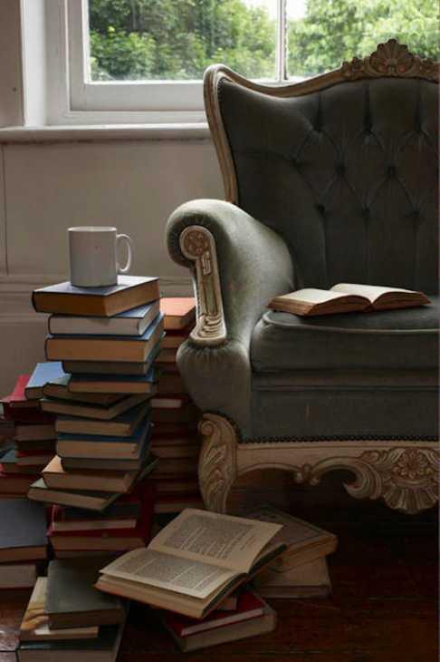 Una pila di libri accanto alla poltrona