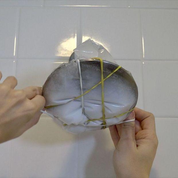 Legare un sacchetto ripieno di aceto e bicarbonato al soffione, da diybitofeverything.com