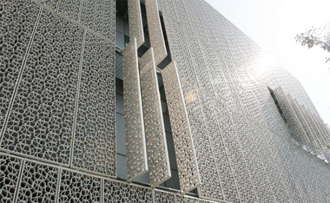 Edificio con facciata in pannelli grigliati di ceramica policroma di Ceipo