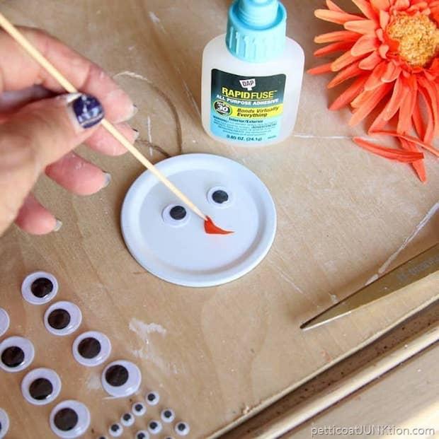 Trasformare i coperchi in decorazioni natalizie a forma di pupazzo di neve, da petticoatjunktion.com
