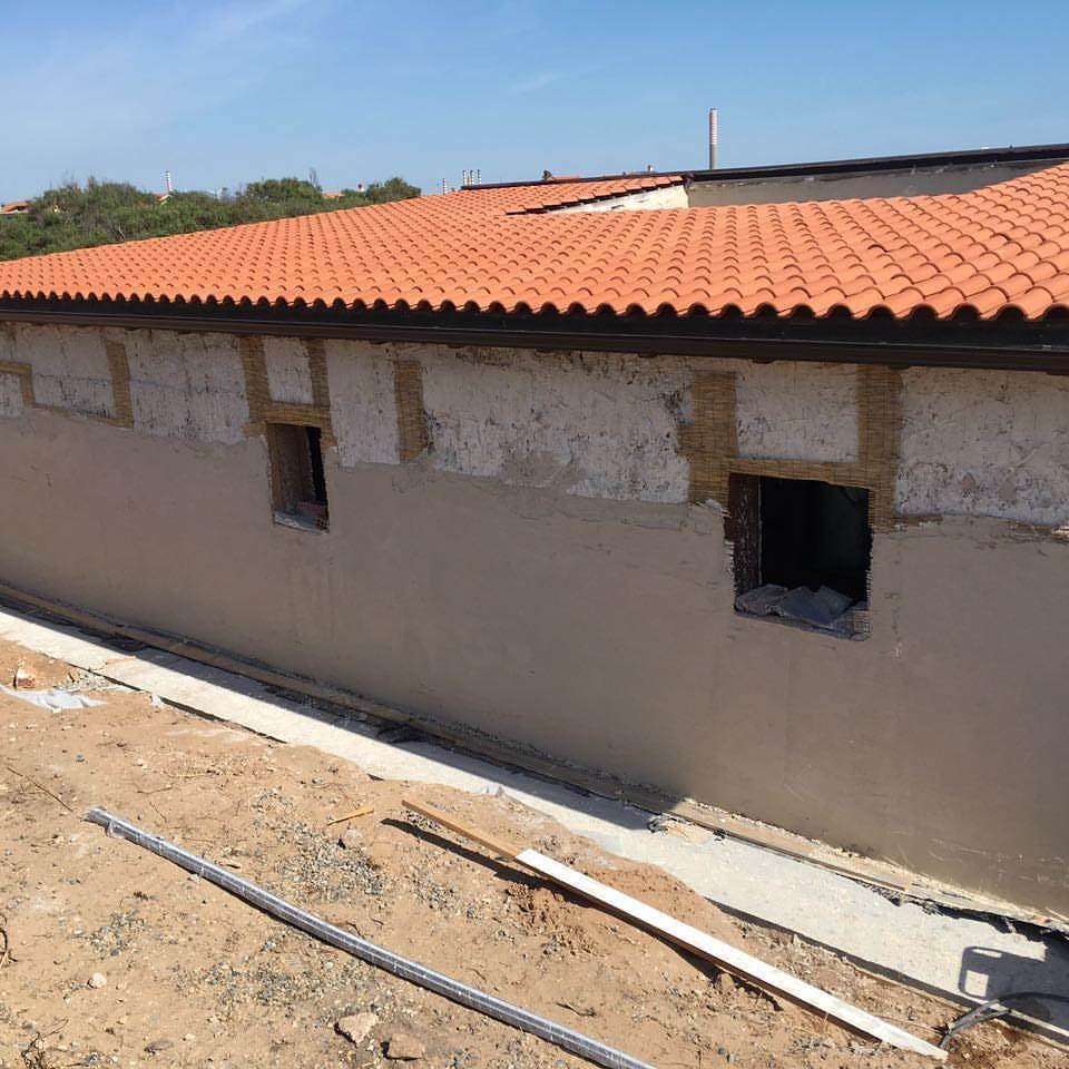 Stesura degli intonaci a calce su un edificio in costruzione di Archética