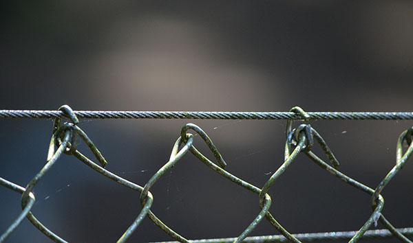 Dettaglio del bordo superiore di una recinzione di rete metallica