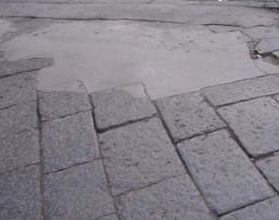 Pavimentazione in basalto con rappezzo in cemento
