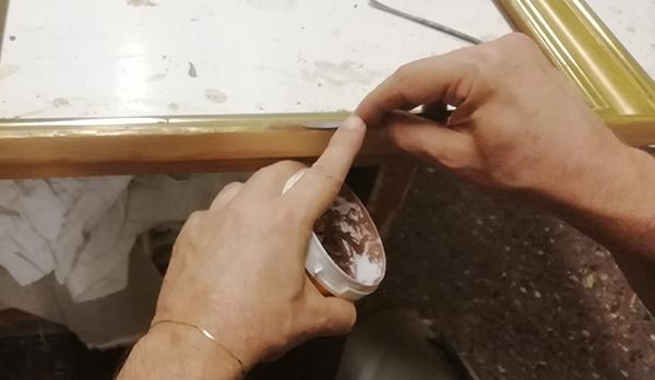 A restorer applies the colored putty with a spatula