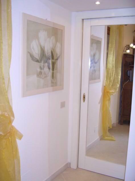 Superfici specchiate: esempio di specchio applicato su porta scorrevole a scomparsa