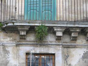 fenomeno di una pianta infestante su ballatoio costituito da elementi in pietra scolpiti a vista