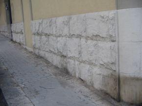 macchie e segni evidenti sulla zoccolatura in pietra di un fabbricato