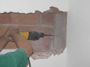 esecuzione del vano nel muro e dei fori per le aste filettate