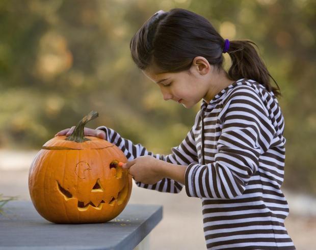Ragazza intenta a modellare una zucca per Halloween